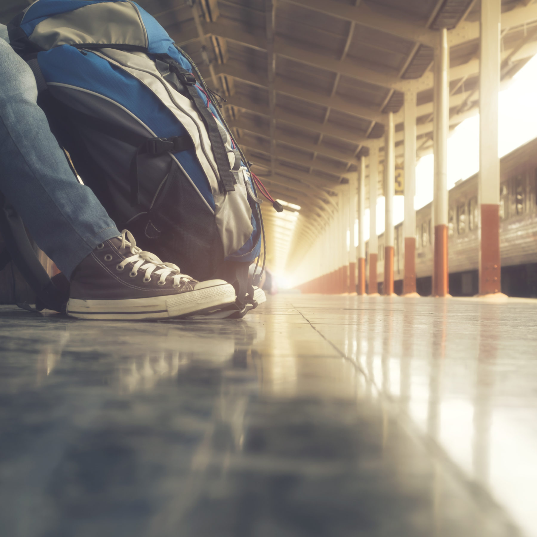 Traveler wearing backpack waiting for a train at trainstation and planing for next trip.Vintage tone, Retro filter effect, Soft focus, Low light.(selective focus)