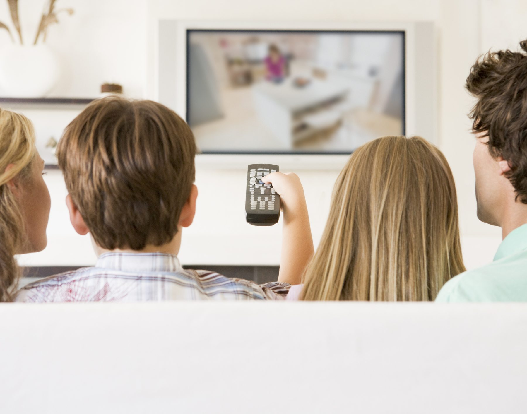 Family in living room with remote control and flat screen television